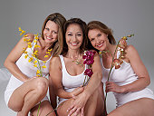Three mature women, holding flowers, smiling, portrait