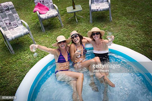 Three mature women sitting in paddling pool, drinking wine, elevated view