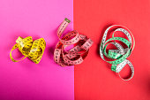 Three measuring tape on red and pink background