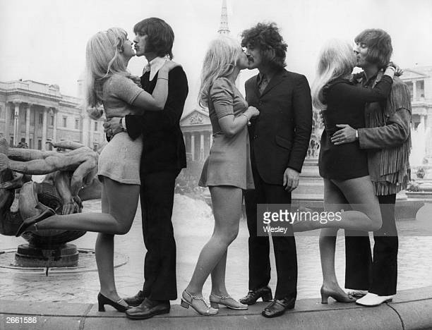 Three members of English pop group The Tremeloes Chip Hawkes Alan Blakley and Dave Munden kissing their brides Carol Dilworth Lyn Stevens and Andree...