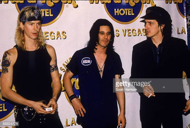 Three members of the American rock and roll group Guns N' Roses in front of a Hard Rock Cafe banner Las Vegas Nevada 1992 From left Duff McKagan...