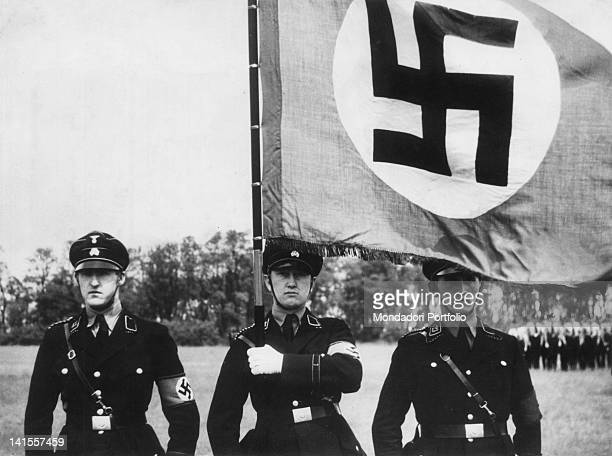 Three members of the German SS with the Nazi flag at a military parade in Munich Munich 1926