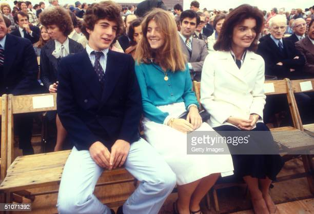 Three Kennedys sit together on wooden folding chair at an unspecified outdoor event late 1970s From left John F Kennedy Jr his sister Caroline...
