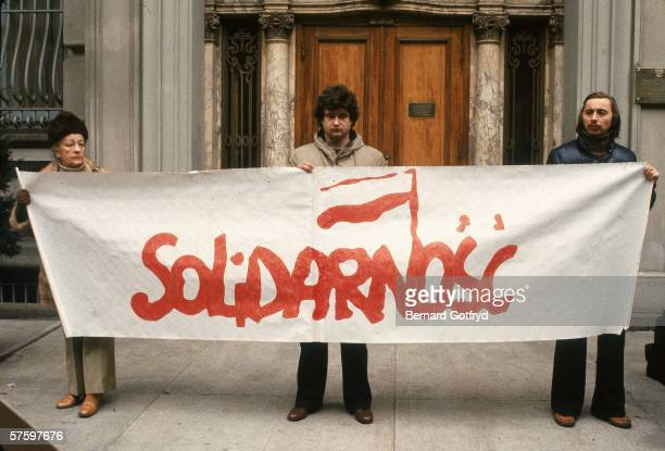 Three somberlooking members of the union hold a banner for Solidarnosc the Independent Selfgoverning Trade Union Poland 1980s