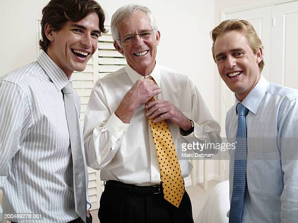 Three men adjusting ties, smiling, portrait