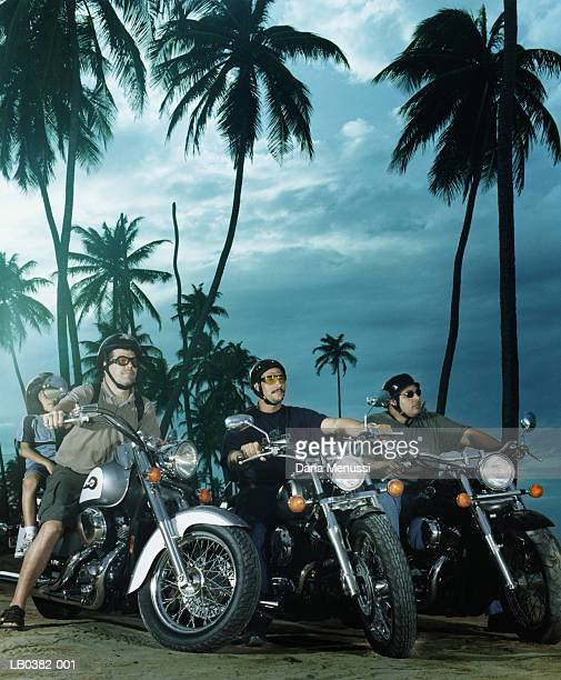Three men and boy (6-8) sitting on motorbikes by palm trees