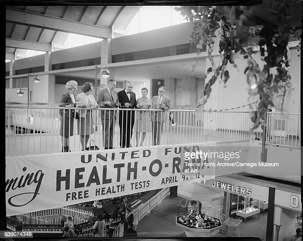 Three men and three women cutting ribbon on balcony in Allegheny Center Mall with banner for United Fund's HealthORama circa 19651975