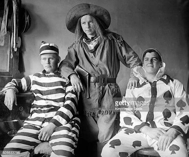 Three men are costumed as a jail prisoner Annie Oakley and spade playing card