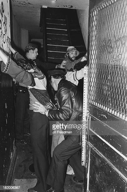 Three men are frisked by police officers in an apartment block hallway in the Lower East Side New York City circa 1979