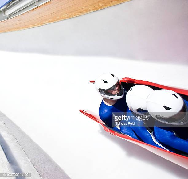 Three men bobsled racing down track, high angle view (blurred motion)