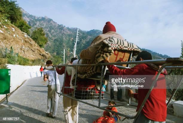Three men carrying a person on a palki Vaishno Devi Temple Katra Jammu And Kashmir India