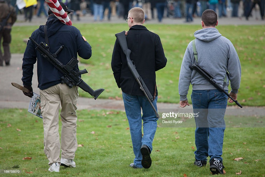 Three men carrying guns leave a pro-gun rally at the capitol building on January 19, 2013 in Olympia, Washington. The Guns Across America national campaign drew thousands of protesters to state capitols, including over 1,000 in Olympia.