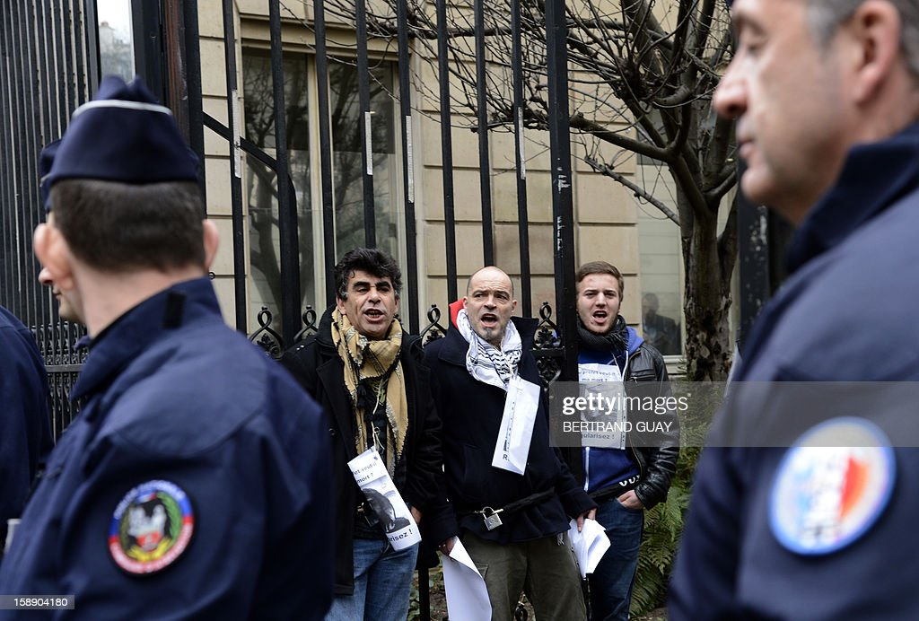 Three men chain themselves to the gate of the Socialist party (PS) headquarters on January 3, 2013 in Paris. The men call for the regularization of immigrants in the French northern city of Lille. Protestors claimed to act in support of Lille's fifty people who have begun a hunger strike since early November. AFP PHOTO / BERTRAND GUAY