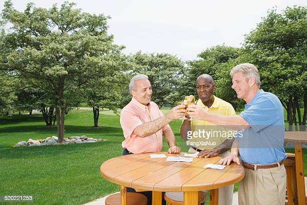 Three men cheering after golf match