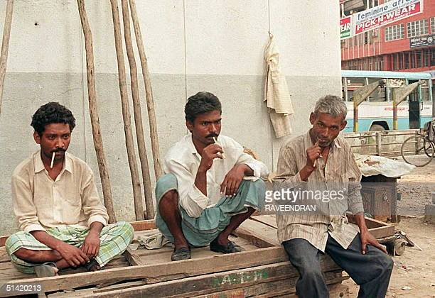 Three men chew on a Neem twig in New Delhi 17 September to clean their teeth in the traditional Indian manner Neem or Margosa is widely used here and...