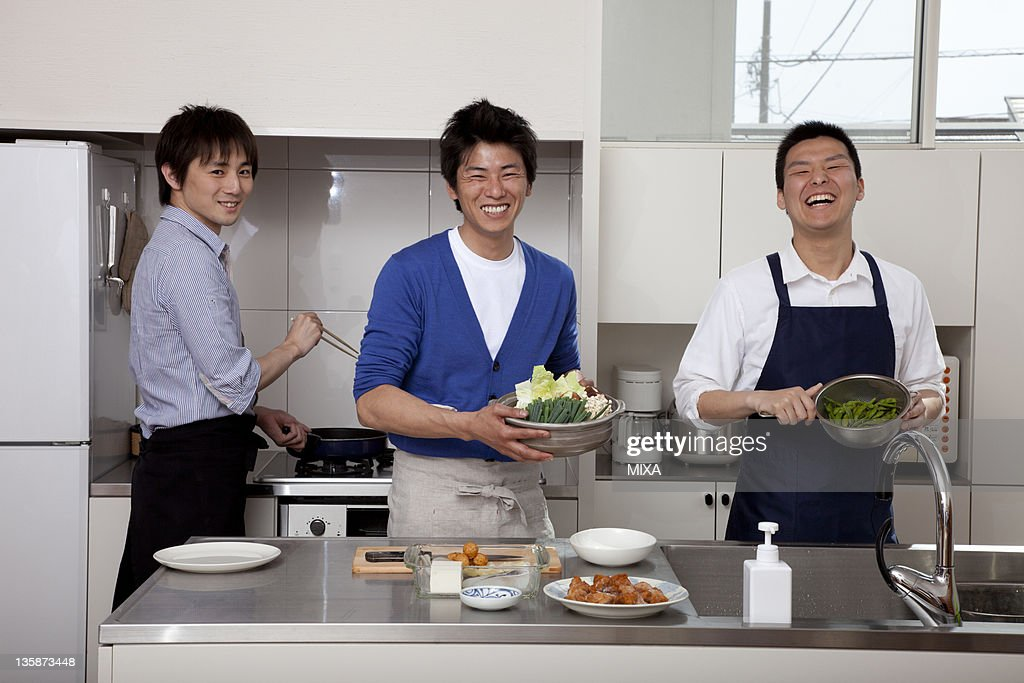 Three men cooking together in the kitchen : Stock Photo