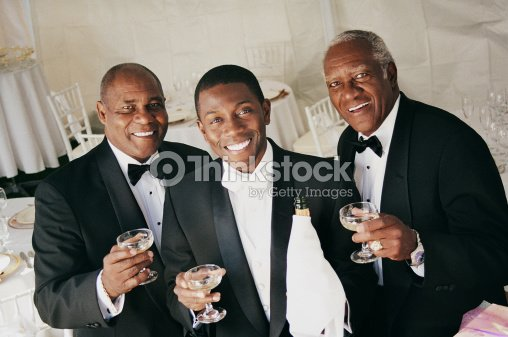 Three Men Drink A Toast Indoors At A Wedding Reception Stock Photo