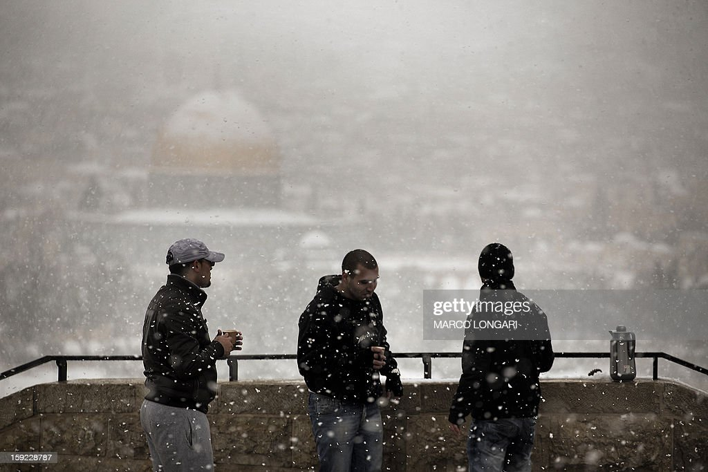 Three men drink coffee under the snow near the Al-Aqsa Mosque compound in the old city of Jerusalem on January 10, 2013. Jerusalem was transformed into a winter wonderland after heavy overnight snowfall turned the Holy City and much of the region white, bringing hordes of excited children onto the streets.