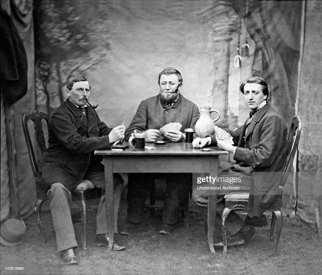 Three men drinking, smoking, and playing cards at a table, 1880s.
