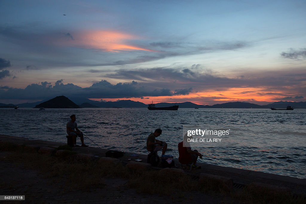 Three men fish as the the sun sets over Victoria Harbour in Hong Kong on June 26, 2016. The official Hong Kong Observatory issued a hot weather warning on June 26 as a subtropical ridge continued to bring very hot weather to southern China. / AFP / DALE