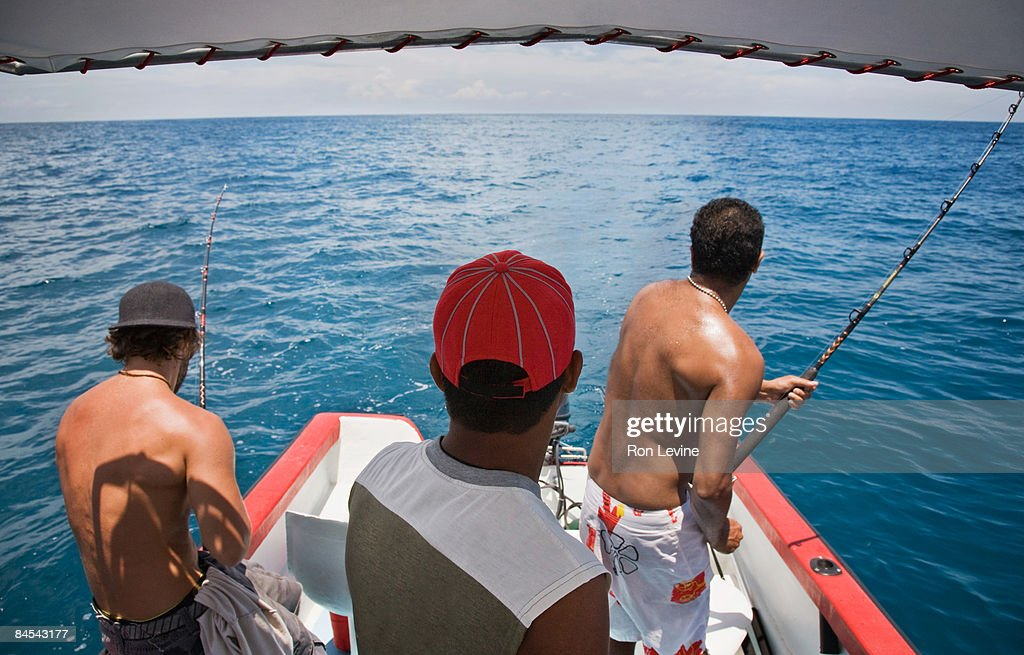 Three men fishing in the ocean, rear view : Stock Photo