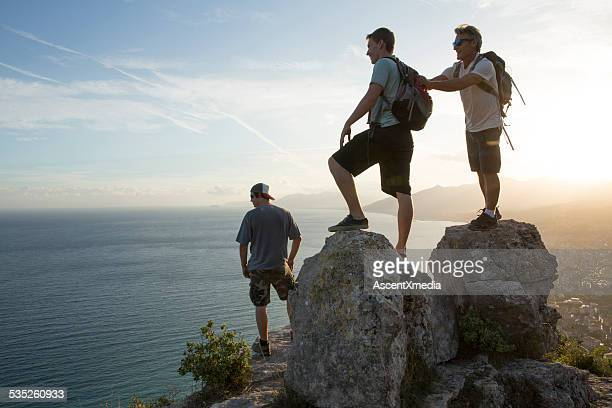 Three men goof around at top of hike