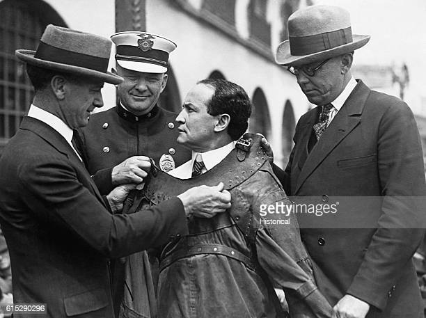 Three men help famed magician and escapeartist Harry Houdini into a leather straitjacket