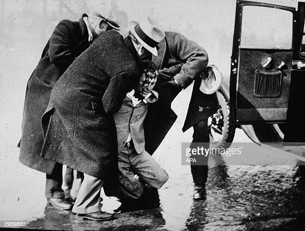 Three men help Harry Bennett head of Ford Motor Co's secret service into an automobile after he was injured during a riot at the Ford Motor Co River...