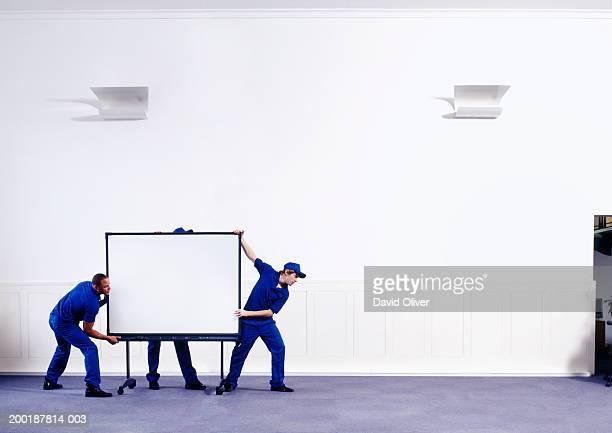 Three men in corridor moving screen