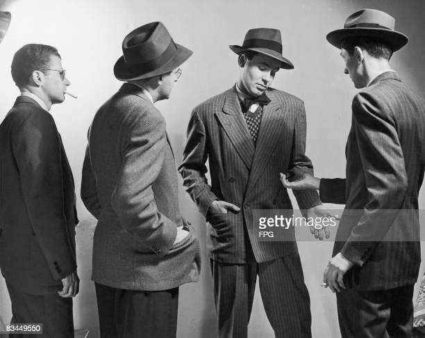 Three men in suits demanding something from a fourth who is protesting he does not have it circa 1930