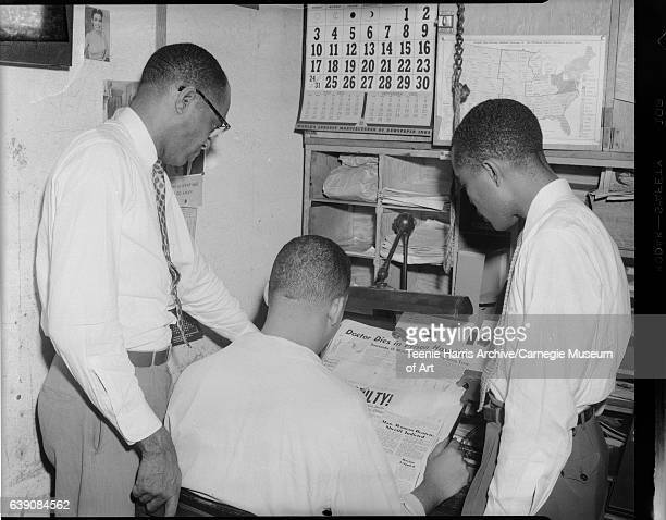 Three men including man on left wearing patterned necktie and eyeglasses gathered around desk reading newspaper inscribed 'Doctor Dies in Prison...