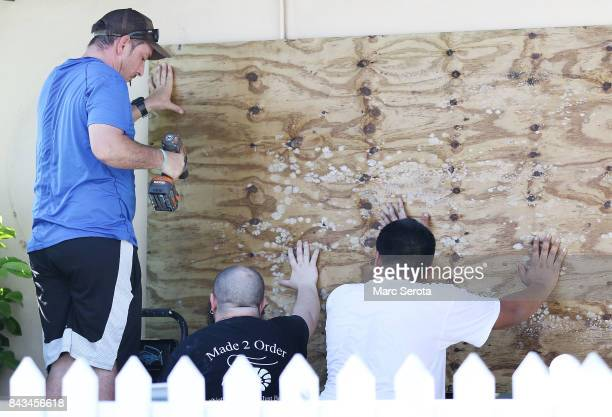 Three men install hurricane shutters at the Made 2 Order Restuarant in Islamorada Florida on September 6 2017 The storm has grown to a category 5 and...