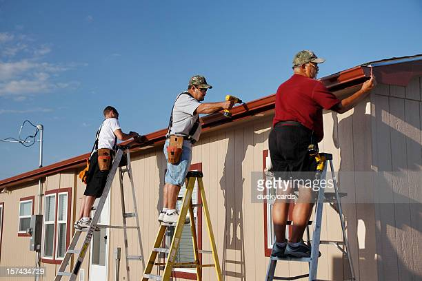 Three Men Installing Seamless Aluminum Gutters on Home