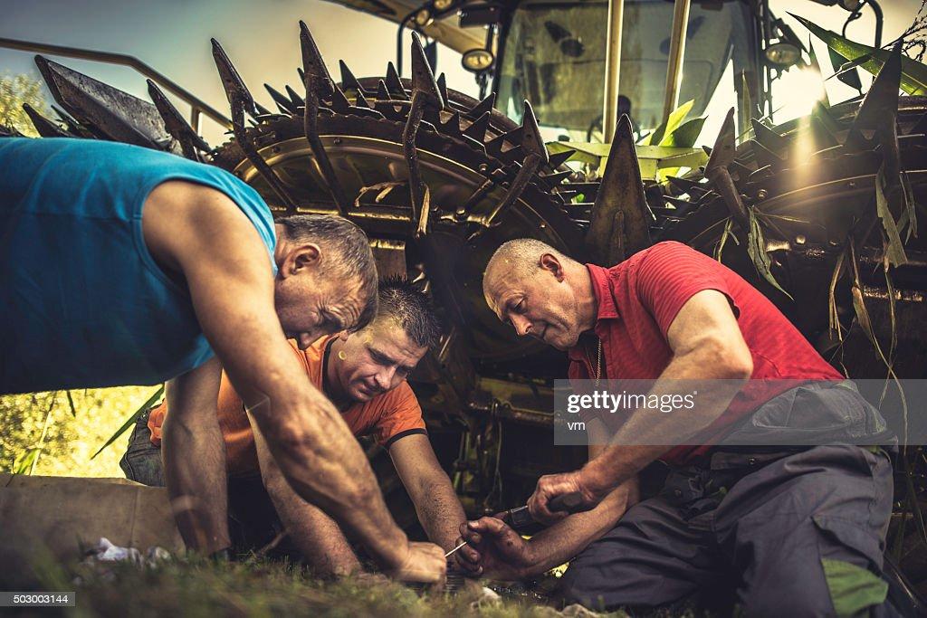 Three men kneeling by a combine harvester repairing it