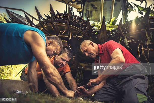 Three men kneeling by a combine harvester repairing it