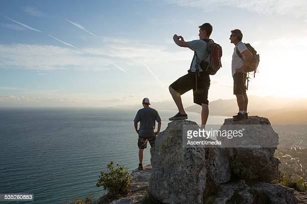 Three men look out to view at top of hike