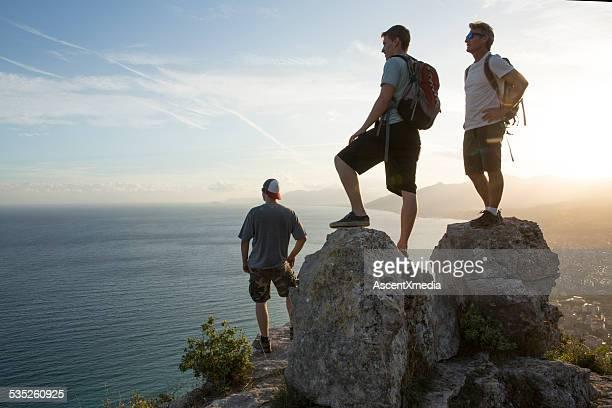 Drei Männer halten Sie zum Anzeigen oben auf der Wanderung