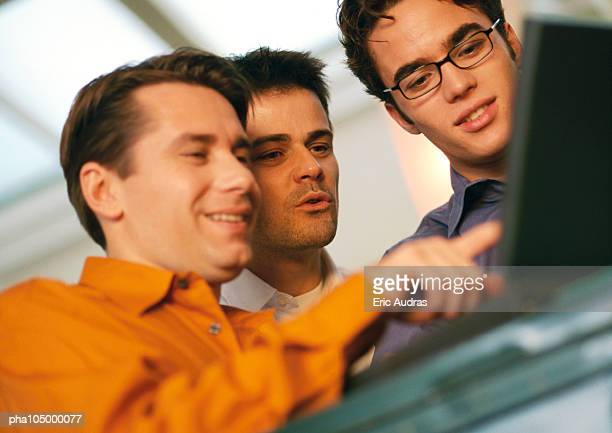 Three men looking at laptop