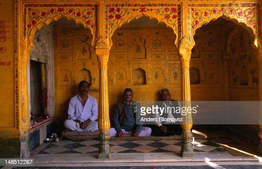 Three men meditate at the yellow temple by Vishram Ghat.