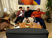 Three Men on a Couch Watching Television