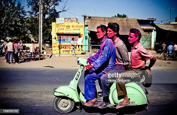 Three men on a motorbike covered with coloured powdered dye and coloured water that people throw on each other during Holi on March 1 at Jaipur India