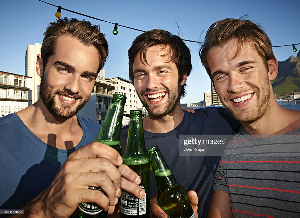 Three men on roof top drinking bottled beer : Stock Photo