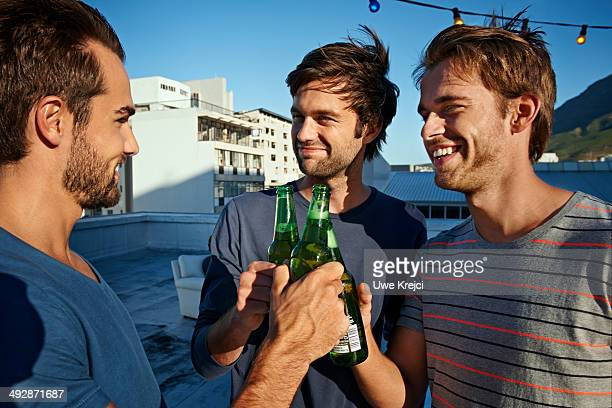 Three men on roof top drinking bottled beer