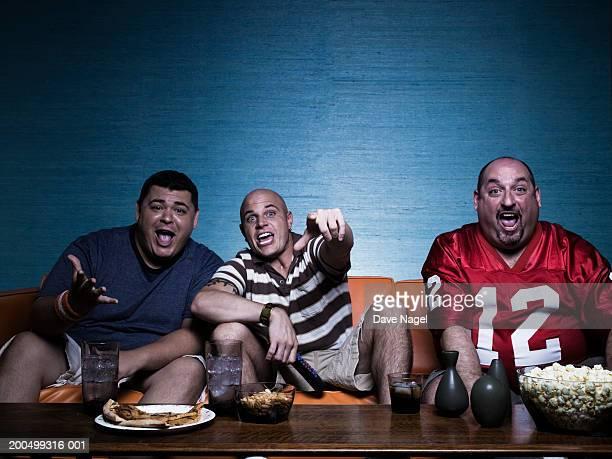 Three men on sofa, watching television, portrait