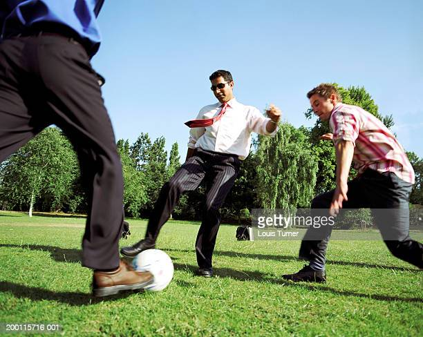 Three men playing football in park, blurred motion