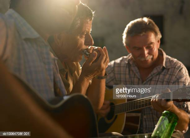 Three men playing instruments at sunset (differential focus)