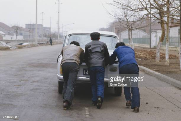 Three men pushing a car which has run out of fuel in the city of Weihai in eastern Shandong province China January 1986