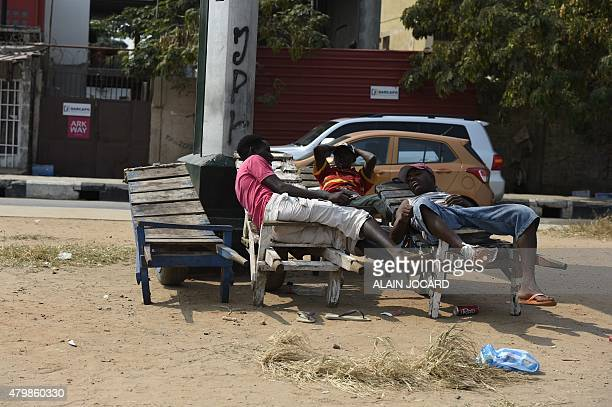 Three men relax on wooden carts in a street of Luanda on July 3 2015 AFP PHOTO/ ALAIN JOCARD