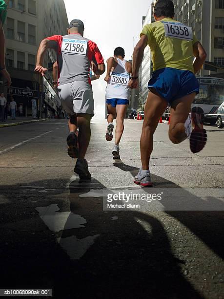 Three men running in marathon, rear view