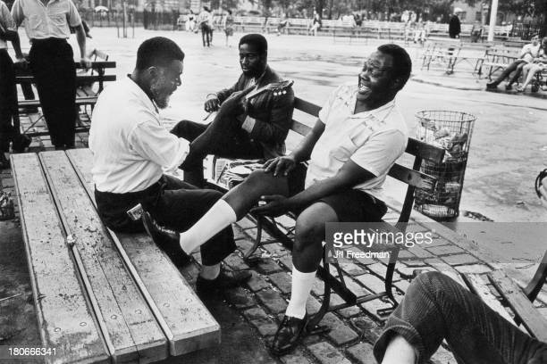 Three men share a joke in Tompkins Square Park Alphabet City New York City circa 1967